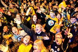Fans sing in unison during a playoff pep rally for the Steelers at Stage AE on the North Shore on Friday.