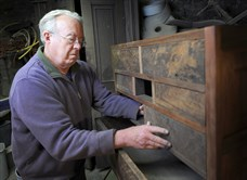 Tom Buckelew of Beeson Hill Antiques works on a chest of drawers in his home workshop in Uniontown.