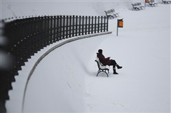 A woman sits on a bench Monday at the government district after a heavy snowfall  in Berlin.