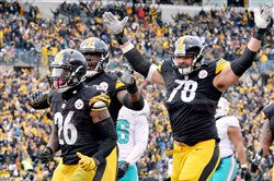 Alejandro Villanueva celebrates a touchdown by Le'Veon Bell against the Dolphins in the second quarter of the AFC wild card game. Both players have yet to sign their one-year contracts and could be absent from training camp.