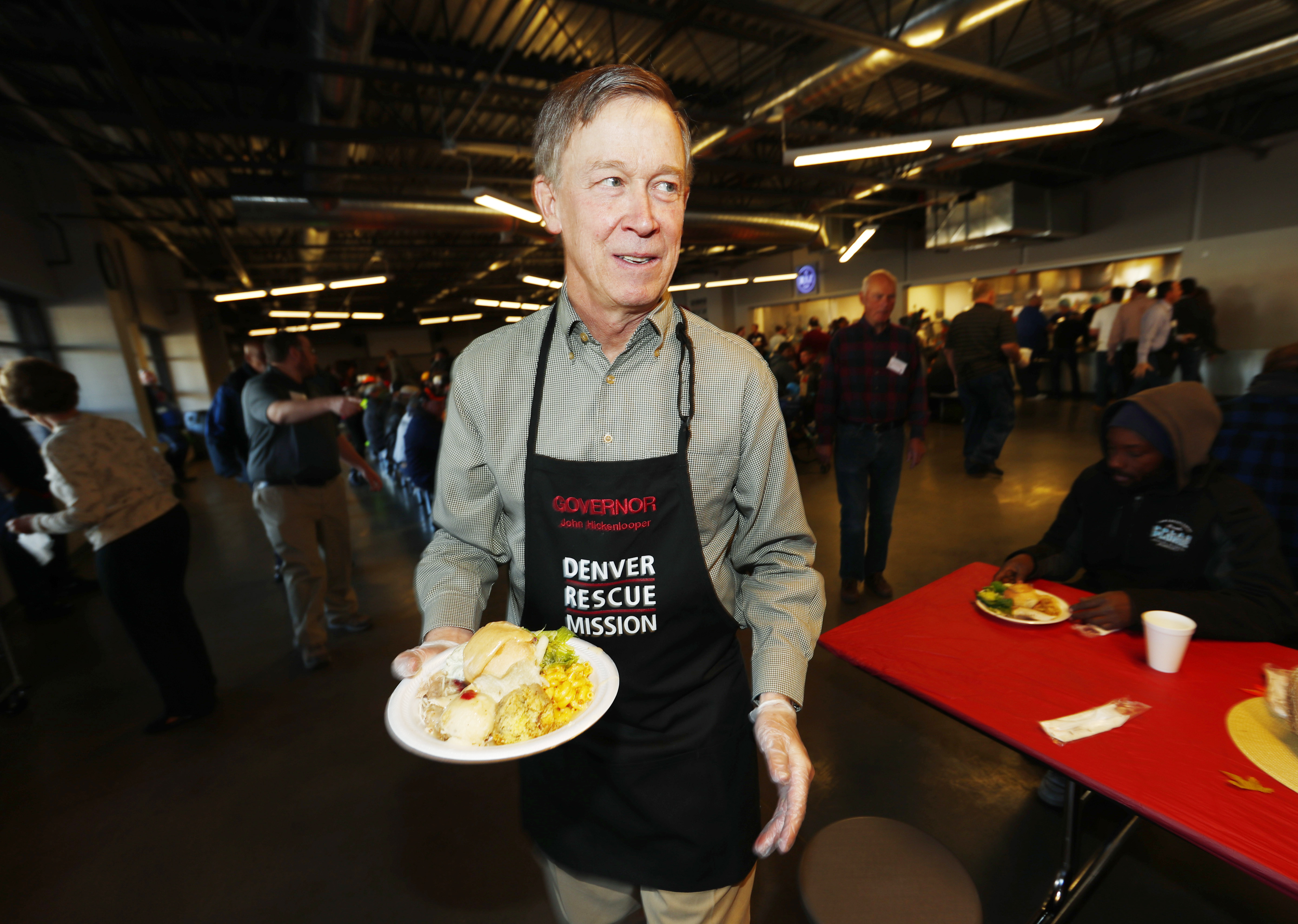 Clean Air Colorado In this Wednesday, Nov. 23, 2016, file photograph, Colorado Gov. John Hickenlooper carries a plate of food as he helps to serve the great Thanksgiving banquet to more than 500 homeless and poor men, women and children at the rescue mission in downtown Denver. Citing backlash from Republicans, Colorado's Democratic governor, Hickenlooper, said Tuesday, Jan. 10, 2017, he has abandoned the idea of issuing an executive order to seek a one-third cut in greenhouse gas emissions from power plants.