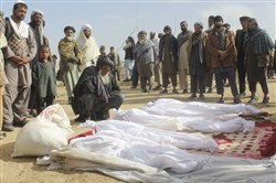In this Nov. 4, 2016, file photo, Afghan villagers gather around several victims' bodies who were killed during clashes between Taliban and Afghan security forces in the Taliban-controlled Buz-e Kandahari village in Kunduz province, Afghanistan.
