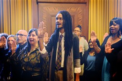 Julian Arney, center, of Friendship and other members of the Pittsburgh's LGBTQIA+ Advisory Council swear in at the City-County Building on Friday. 16 members of the Advisory Council are in charge of taking a comprehensive approach to meet the needs of the entire LGBTQIA+ community.
