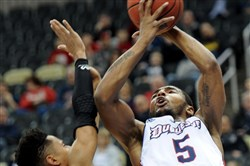 Duquesne's Emile Blackman (cq) shoots over Darrell Davis during their loss to Dayton Saturday.