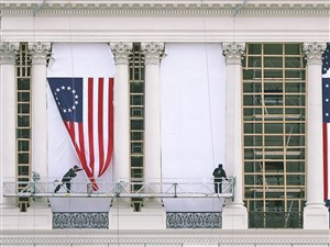 Workers hang an early version of the American flag on the U.S. Capitol to be used as part of the backdrop to the presidential inauguration for President elect Donald Trump as he prepares to take the reins of power.