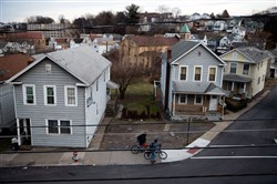 People walk their bicycles through a residential neighborhood in Wilkes-Barre, Pa. Luzerne County voters have long backed Democrats for president, including President Obama. In 2016, the county flipped big for Republican Donald Trump, supplying roughly a third of his margin of victory for the entire state.