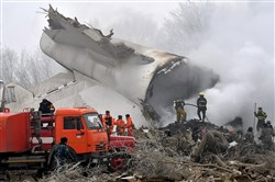 Kyrgyz Emergency Ministry officials and firefighters work Monday among remains of a crashed Turkish Boeing 747 cargo plane at a residential area outside Bishkek, Kyrgyzstan.