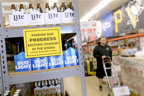 Landyn Klein, manager with Save-Mor Beer & Pop Warehouse in Squirrel Hill, gets another case to stock shelves with six-packs of beer Tuesday.