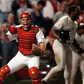 In this Oct. 4, 1996, file photo, Rangers catcher Ivan Rodriguez reacts after tagging out the Yankees' Tim Raines in Game 3 of a playoff series. Both Rodriguez and Raines were elected to the Baseball Hall of Fame.