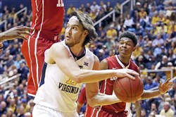 Nathan Adrian of West Virginia looks to pass against the Oklahoma Sooners Wedneday night at WVU Coliseum in Morgantown, W.Va. Oklahoma upset No. 7 West. Virginia, 89-97.