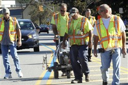 Employees with the Wayne, N.J., Department of Public Works paint a blue line in the middle of a double-yellow line on a roadway in September. Blue lines have been appearing on streets in New Jersey and many other states in recent months to show support for law enforcement.