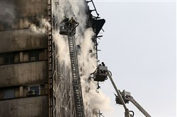 Iranian firefighters work to extinguish fire of the Plasco building in central Tehran, Iran, Thursday, Jan. 19, 2017. A high-rise building in Tehran engulfed by a fire collapsed on Thursday as scores of firefighters battled the blaze.
