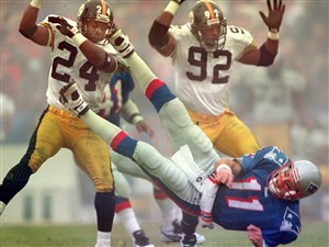 Pittsburgh Steelers safety Chris Oldham (24) and linebacker Jason Gildon toss New England Patriots quarterback Drew Bledsoe to the turf at foggy Foxboro Stadium during an AFC playoff game January 5, 1997.