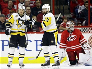 Carl Hagelin, left, is congratulated by teammate Nick Bonino following Hagelin's goal against Hurricanes' goalie Cam Ward, right, during the second period Friday night in Raleigh, N.C.