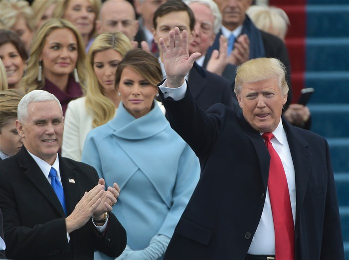 Vice-president elect Mike Pence (L) applauds as President-elect Donald Trump waves to the crowd as he arrives on the platform at the US Capitol in Washington, DC, on January 20, 2017, before his swearing-in ceremony. / AFP PHOTO / Mandel NGANMANDEL NGAN/AFP/Getty Images