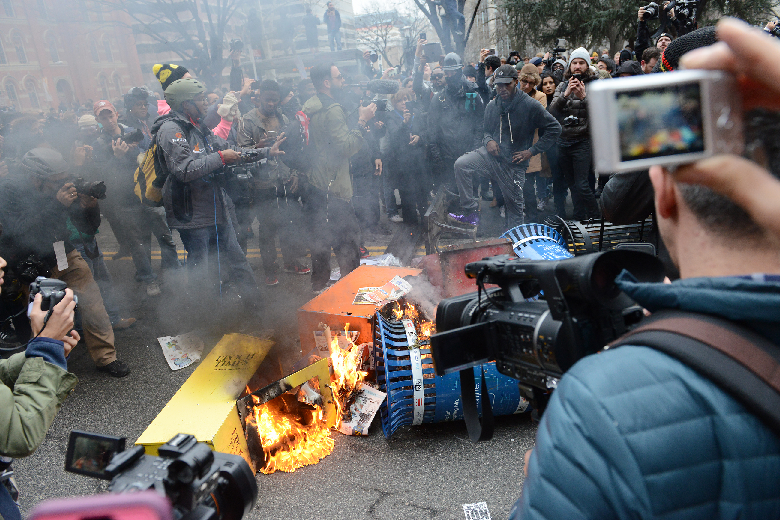 20170120rldInauguration15 A crowd gathers around a garbage can fire lit by protesters at 13th and K Streets NW in Washington, DC, on Friday afternoon.