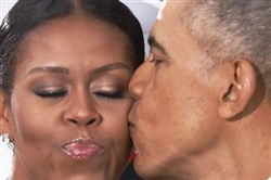 President Barack Obama kisses first lady Michelle Obama as they wait for President-elect Donald Trump and his wife Melania Trump at the White House, Friday.