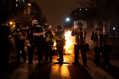 Police officers take up a position in a crosswalk on the night of President Donald Trump's inauguration, in Washington, D.C. on Friday night.