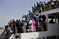 A ferry carrying people who fled Gambia arrives Sunday at the port in Banjul, Gambia, one day after Gambia's defeated leader Yahya Jammeh left the country.