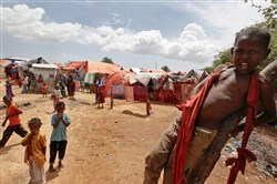 In this photo taken Nov. 16, 2016, Somali children who were repatriated to Somalia from Kenya's Dadaab camp play in front of makeshift shelters in the Daryeel camp for the displaced in Mogadishu, Somalia.