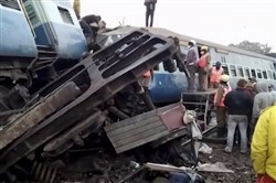 In this image from video, rescuers stand around coaches of a derailed passenger train in Kuneru, southern India, on Sunday.