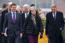 British Prime Minister Theresa May, center, arrives with colleagues, British Chancellor of the Exchequer Philip Hammond, right, and British Business, Energy and Industrial Strategy Secretary Greg Clark, left, to hold a regional Cabinet meeting in Runcorn, northwest England, on Monday.