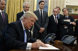 From left, White House Chief of Staff Reince Priebus, National Trade Council adviser Peter Navarro, Senior Adviser Jared Kushner, policy adviser Stephen Miller, and chief strategist Steve Bannon watch as President Donald Trump signs an executive order in the Oval Office of the White House.