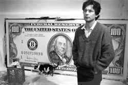 Artist J.S.G. Boggs in his studio with a $100 bill that he painted.