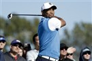 Tiger Woods watches his tee shot during the first round of the Farmers Insurance Open Thursday.