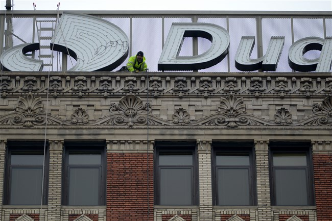 A man works atop the Duquesne Light Corporate Headquarters last month on Seventh Avenue, Downtown, preparing for the removal of the old sign to make room for a replacement.