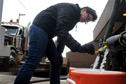 Rosette Cooley of Shadyside fills water buckets from a water buffalo at Fire Station 6 in Lawrenceville on Wednesday. Insufficient chlorine in Pittsburgh's public water supply led to the closure of nearly two dozen grade schools and a boil-water advisory in about 20 neighborhoods.
