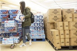 Mengxi Tan, a student at Carnegie Mellon University and resident of Shadyside, stocks up on bottled water following the the water advisory issued Tuesday evening.