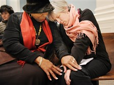 Deborah Benton, left, of the South Hills and Ruth Green of Scotland pray together during a service of Repentance and Reconciliation on Friday at Hicks Chapel at the Pittsburgh Theological Seminary in Highland Park. The prayer service was led by 12 senior pastors and bishops from local Roman Catholic, Orthodox and Protestant churches.