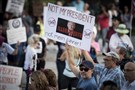 Protesters demonstrate outside Trump Plaza in West Palm Beach, Fla., as President Donald Trump and first lady Melania Trump attend the 60th annual Red Cross Ball at Trump's Mar-a-Lago resort on Saturday.