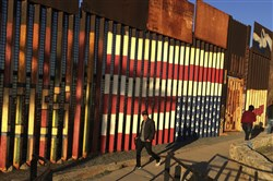 "People walk past a mural painted on a border structure in Tijuana, Mexico, on Wednesday, Jan. 25, 2017. The mural, entitled ""SOS, Deported Veterans,"" was painted in 2013 by artist Amos Gregory to help raise awareness of the plight of deported veterans."
