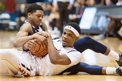 Dachon Burke fights for the ball with Mount St. Mary's guard Junior Robinson, top, on Thursday at Sewall Center.