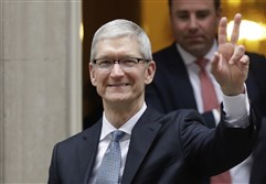 Apple CEO Tim Cook waves at members of the media as he leaves 10 Downing St. in London on Thursday.