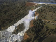 This Saturday aerial photo shows the damaged spillway with eroded hillside in Oroville, Calif. Water will continue to flow over an emergency spillway at the nation's tallest dam for another day or so, officials said Sunday.