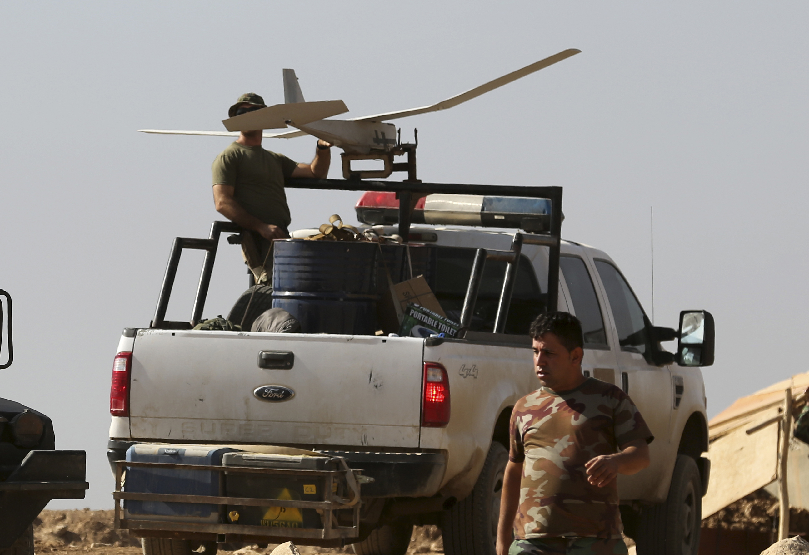 Iraq US-2 In this Friday, Oct. 21, 2016 photo, a U.S. soldier, left, prepares to launch a drone in a joint base with Iraqi army on the outskirts of Mosul, Iraq. Reverberations from President Donald Trump's travel ban and other stances are threatening to undermine future U.S.-Iraqi security cooperation, rattling a key alliance that over the past two years has slowly beaten back the Islamic State group. Iraq's prime minister, Haider al-Abadi, has sought to contain public anger sparked by the ban and by Trump's repeated statements that the Americans should have taken Iraq's oil, as well as his hard line against Iran, a close ally of Baghdad. (AP Photo/Khalid Mohammed)