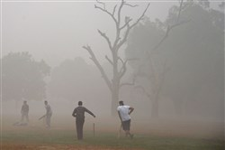 This file photo taken Nov. 6, 2016, shows Indian men playing cricket amid heavy smog in New Delhi.