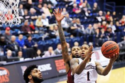 Duquesne's Mike Lewis II takes a shot as Zach Lewis of Massachusetts defends him Wednesday at Palumbo Center.