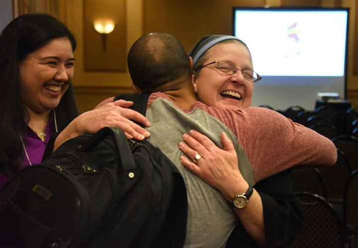20170216dsCatholic0219SundayLocal12-11 Sister Lucy Likasiewicz, of Amarillo, Texas, gives a big hug to Fausto Franco, of Albany, N.Y., after Mass Thursday at the Embassy Suites in Moon. The service and reunion marked the 50th anniversary of a 1967 weekend retreat of Duquesne University students who reported an overpowering experience of the Holy Spirit.