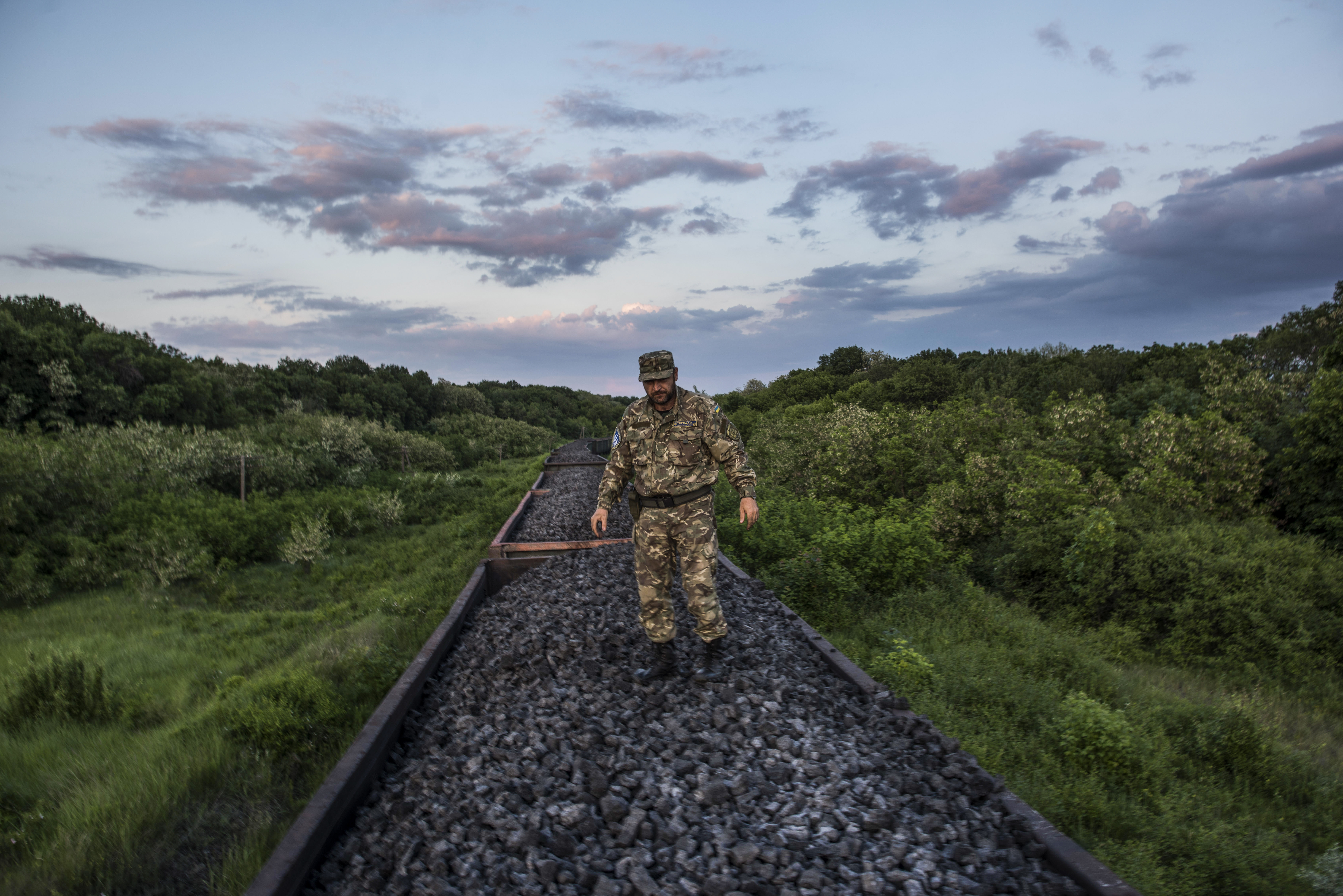 Ukraine-1 FILE - In this Tuesday, June 2, 2015 file photo, Mykola Tsukur, deputy commander of the volunteer Tornado battalion, stands atop a train carrying coking coal from the rebel-held parts of the Luhansk region into the government-controlled area in Orekhove, Ukraine. President Petro Poroshenko on Thursday, Feb. 16, 2017, has pledged to resume coal supplies from separatist-controlled parts of eastern Ukraine. (AP Photo/Evgeniy Maloletka, File)