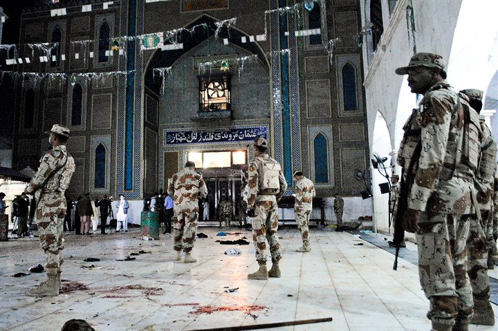 Pakistan-Sufi-shrine-AP-17047688229463 Pakistani soldiers stand guard Thursday after a deadly suicide attack at a shrine in Sehwan, Pakistan. Several women and children were among the dead, officials said.