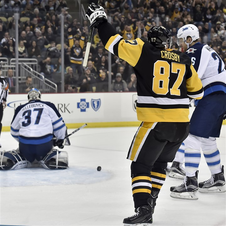 20170216mfpenssports04-2 Penguins center Sidney Crosby celebrates after getting his 1,000th career point Thursday in the first period against Winnipeg at PPG Paints Arena.
