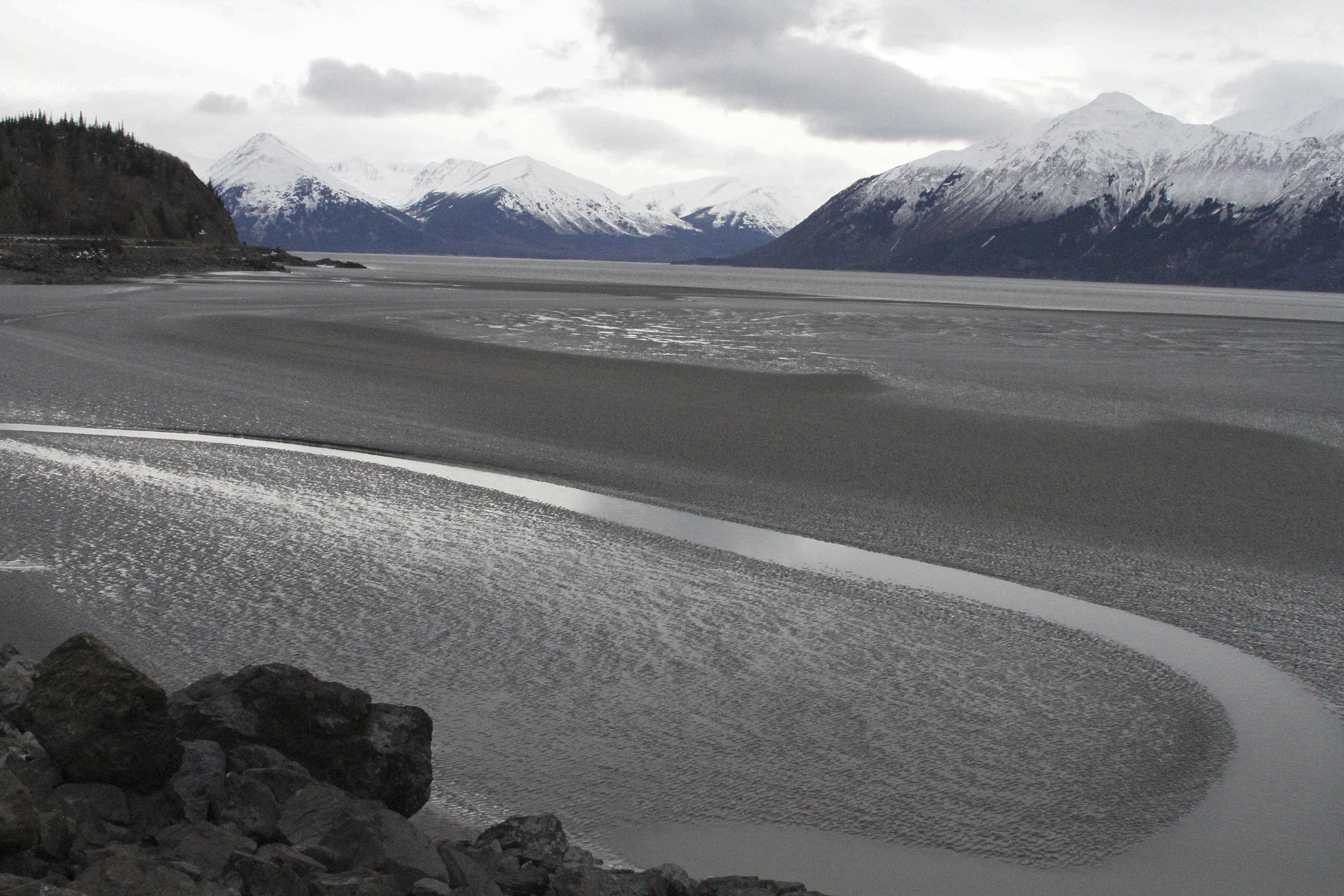 Alaska Underwater Pipeline Leak FILE - In this March 7, 2016, file photo, a ribbon of water cuts through the mud flats of Cook Inlet, just off the shore of Anchorage, Alaska. Natural gas is bubbling up from an underwater pipeline in Alaska's Cook Inlet, discovered on Feb 7, 2017, when a Hilcorp helicopter spotted bubbles at the surface and reported the leak. State regulators say the danger is minimal but the Coast Guard has issued a warning to mariners and federal wildlife authorities have expressed concern about harm to endangered beluga whales. (AP Photo/Mark Thiessen, File)
