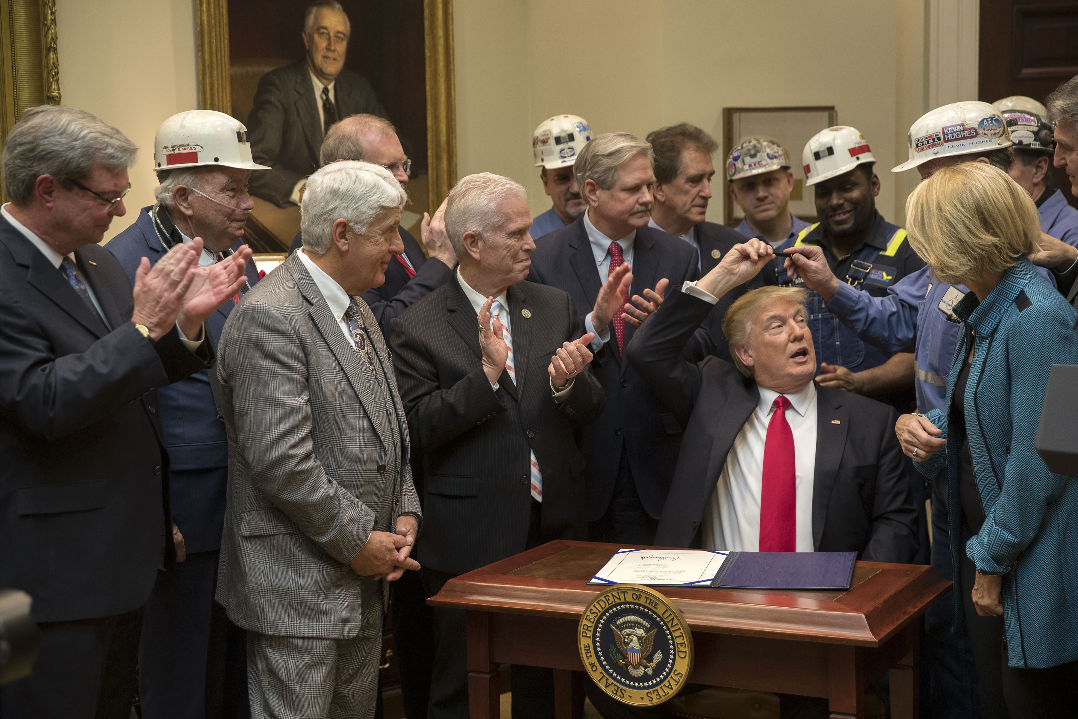 TRUMP COAL ORDER 1-116 President Donald Trump, joined by lawmakers and coal miners, hands off his pen during the signing of a measure to dismantle the Stream Protection Rule, in the Roosevelt Room of the White House in Washington, D.C., on Thursday.