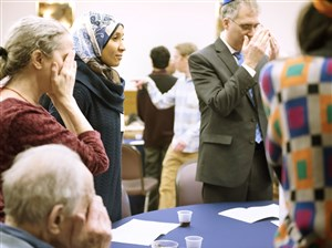 Mona Ramadan, from Regent Square, stands as the other people at her table light the Shabbat candles and make their pre-meal prayers at the Jewish-Muslim Shabbat dinner Friday, at Temple Sinai in Squirrel Hill.