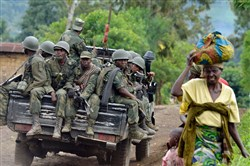 This file photo taken in 2013 toward the Mbuzi hilltop near Rutshuru shows Armed Forces of the Democratic Republic of Congo soldiers sitting at the back of a pickup truck.