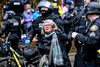 A woman is detained during a protest Monday in Portland, Ore. Thousands of demonstrators turned out across the U.S. to challenge President Donald Trump in a Presidents Day protest dubbed Not My President's Day.